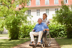 stock-photo-55580776-senior-man-sitting-on-a-wheelchair-with-home-caregiver